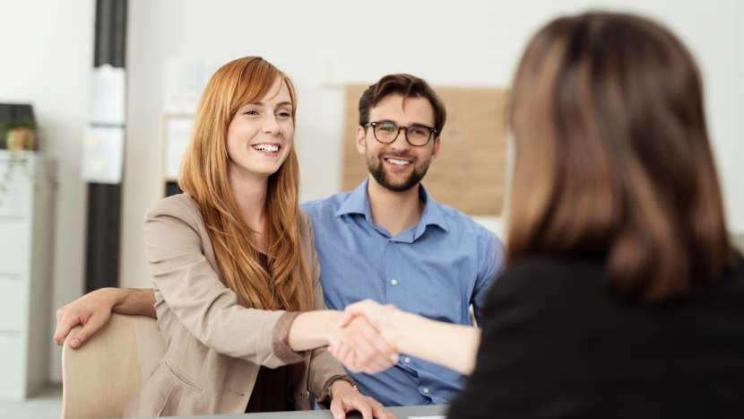 female banker shaking hands with customers sitting at a desk